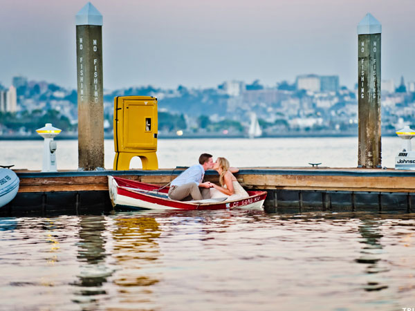 A happy couple on a small boat with the view of San Diego