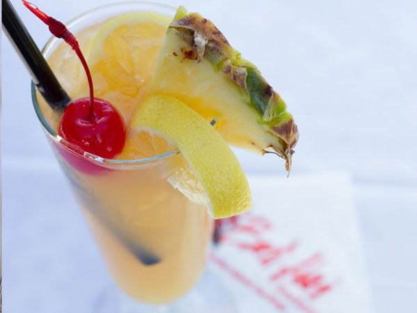 Tropical beverage with pineapple, lemon, and a cherry