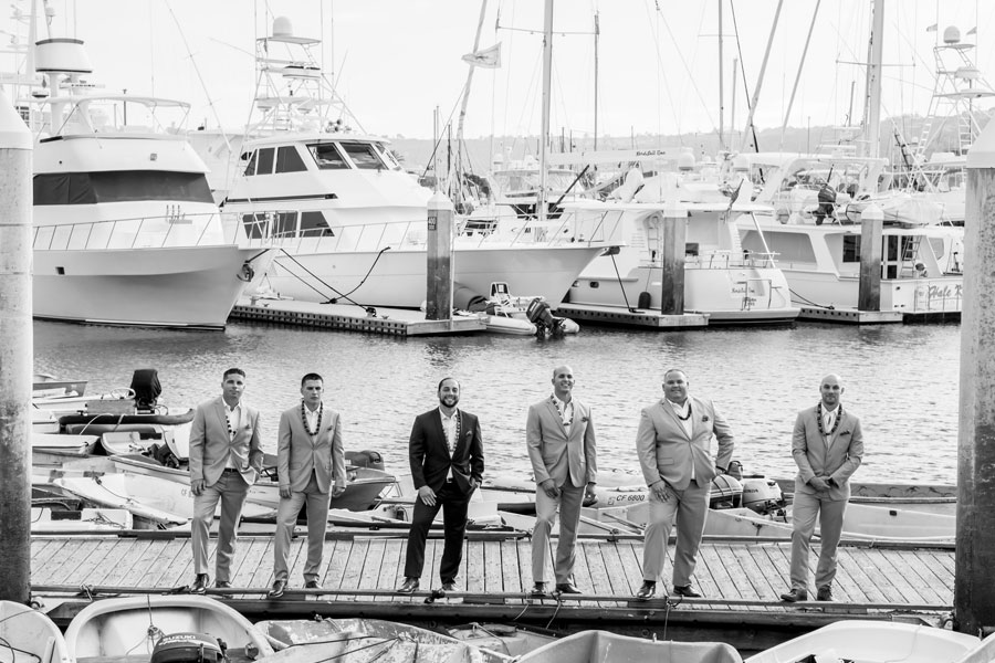 men on a dock in front of boats