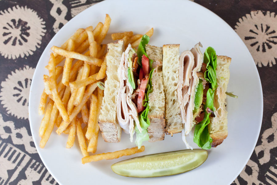 Turkey sandwich with french fries and a pickle