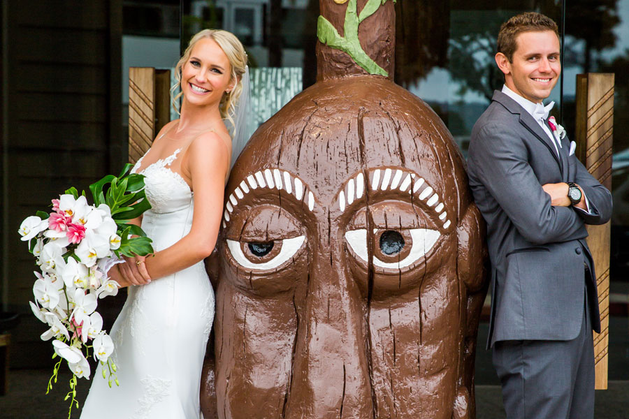 A happy couple after their wedding with a tiki head
