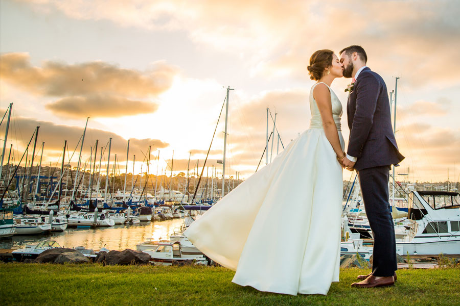 bride and groom near the water and boats