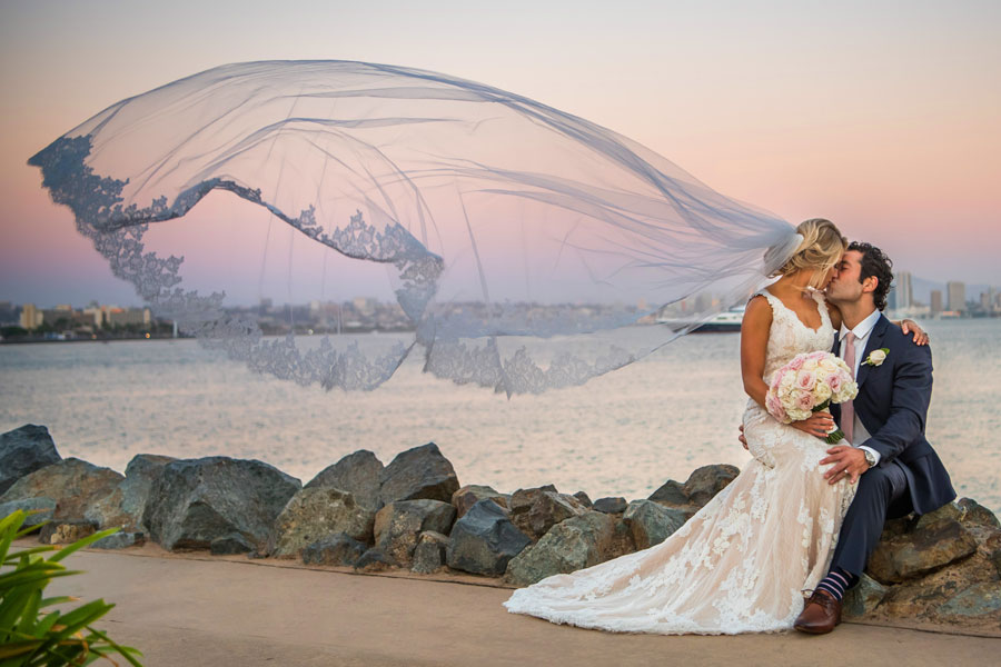 A couple kissing near the water on their wedding day